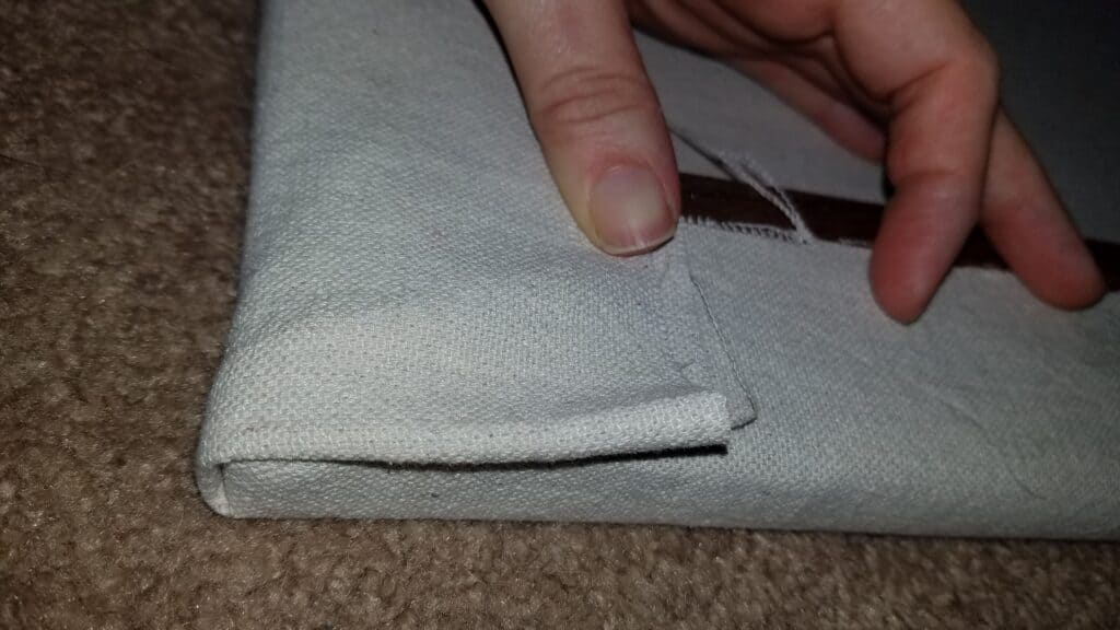 Folding the canvas at the corners in preparation of stapling it down. Make sure the canvas doesn't extend over the edge of the frame. DIY Large wall art, Easy DIY, large wall art ideas, decorating ideas